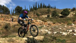 San Antón rider popping off low kicker on trail