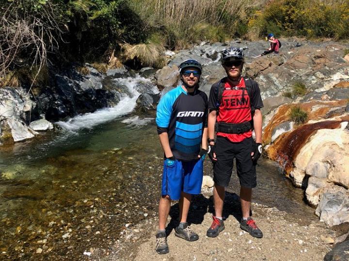 Roman Baths Sierra MTB guides Alexis and Jon posing by the river