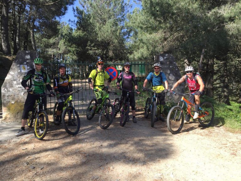 Ojen DH group posing in front of gate at trailhead