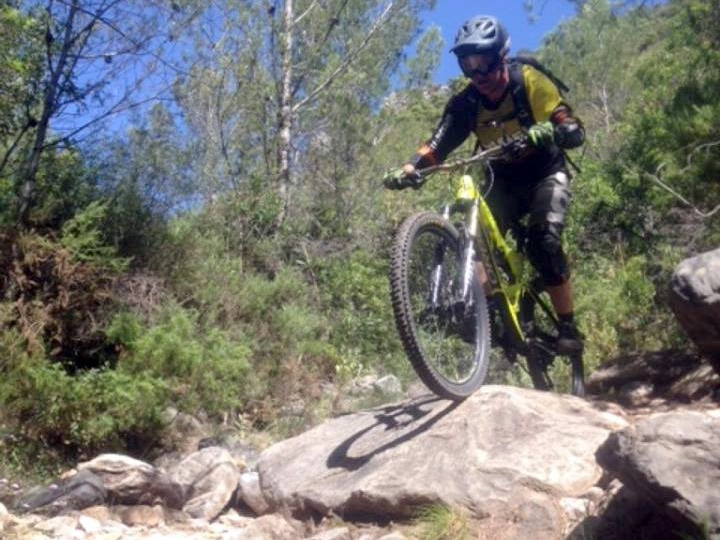 Ojen DH rider over large fixed rocks