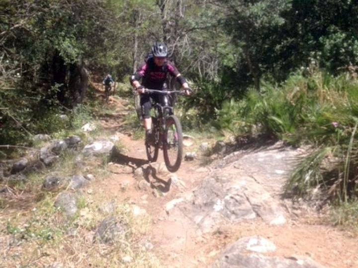 Ojen DH rider popping off rocks on trail